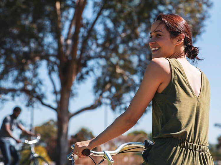 An adult woman in the sun holding her bike.