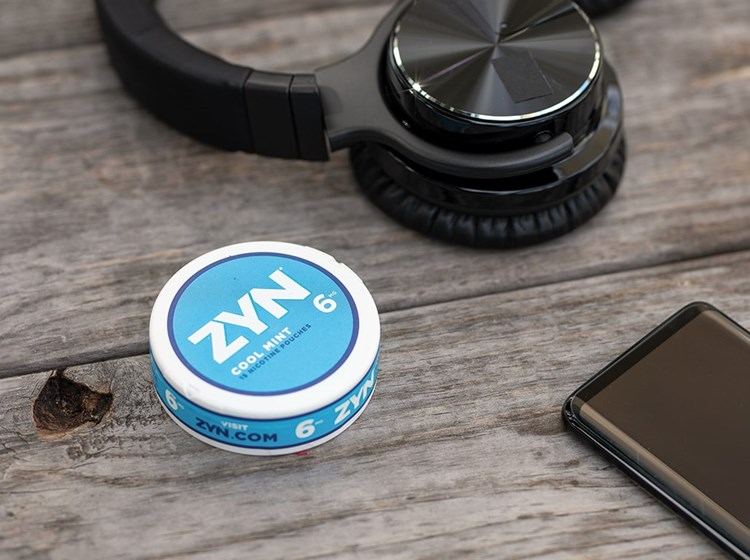 A can of Cool Mint ZYN Tobacco-Free Nicotine Pouches on a table next to a cell phone and headphones.