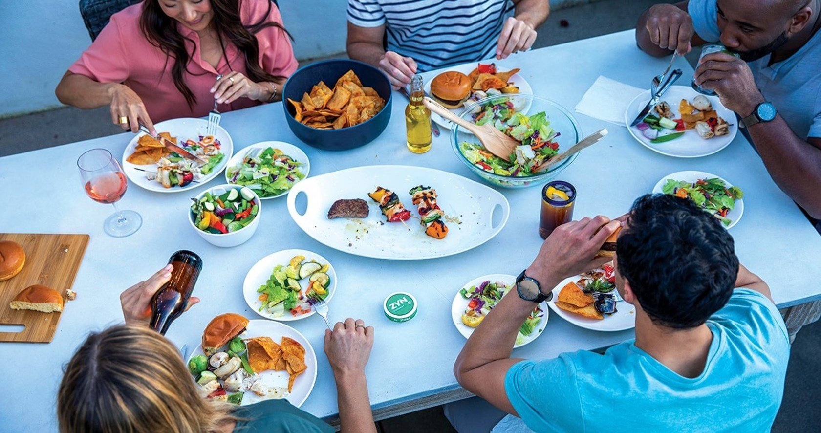 A group of adult friends eating a meal with cans of ZYN Tobacco-Free Nicotine Pouches on the table.